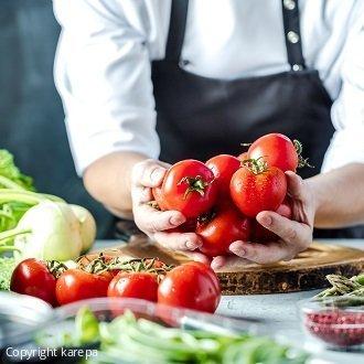Symbolbild für Catering-Broschüre: Koch mit Tomaten in den Händen